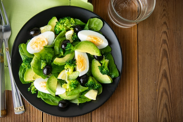 Avocado salad with broccoli, spinach, olives and boiled eggs in black plate, over wooden table.