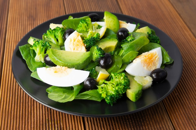Avocado salad with broccoli, spinach, olives and boiled eggs in black plate, wooden table.