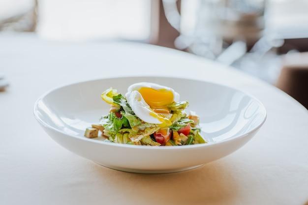 Салат из авокадо с куриным филе и нарезанным яйцом-пашот на белой тарелке на белом столе.