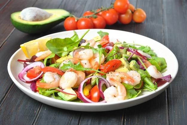 エビ、チェリートマト、赤玉ねぎ、緑の葉のアボカドサラダ