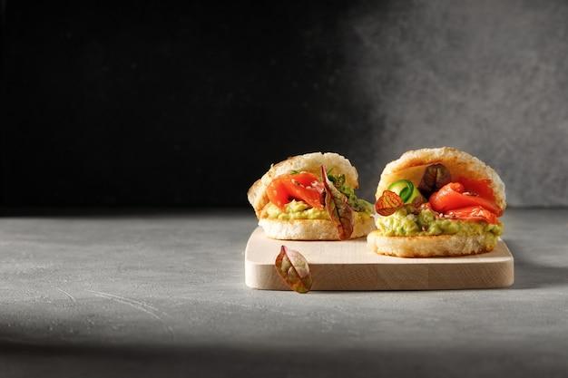 Avocado and salmon bruschetta starter crostini on bread with cucumber on wooden board and dark background