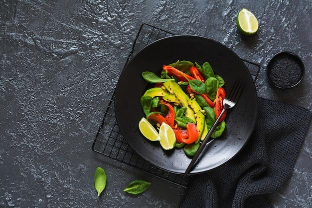 검은 세라믹 접시에 아보카도, 연어, 시금치, 토마토, 잣, 검은 참깨 샐러드. 평면도.