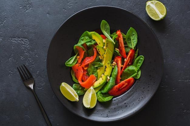 블랙 세라믹 접시에 아보카도, 연어, 시금치, 토마토, 잣, 검은 참깨 샐러드. 평면도.