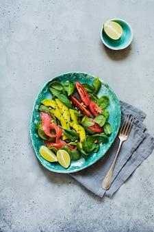 회색 세라믹 접시에 아보카도, 연어, 시금치, 토마토, 잣, 검은 참깨 샐러드. 평면도.