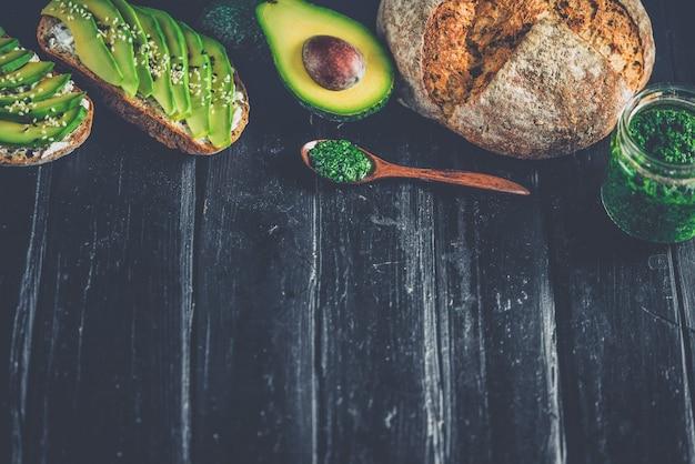 Сэндвич с авокадо на темном ржаном хлебе, приготовленный из свежих нарезанных сверху авокадо. copyspace для вашего текста