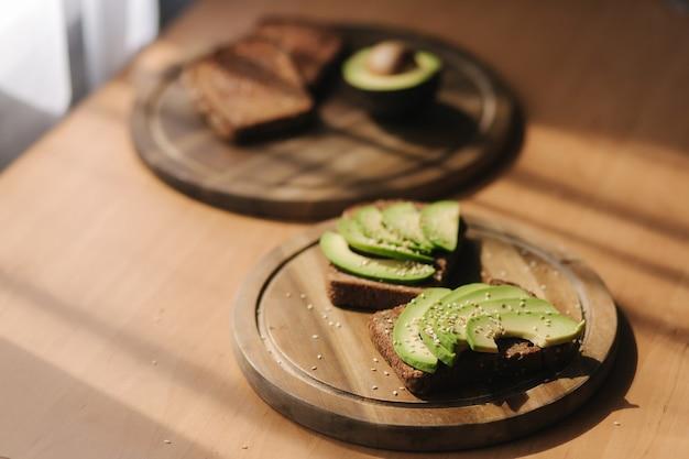 Сэндвич с авокадо на темном ржаном хлебе, приготовленный из свежих нарезанных сверху авокадо. веганский бутерброд на