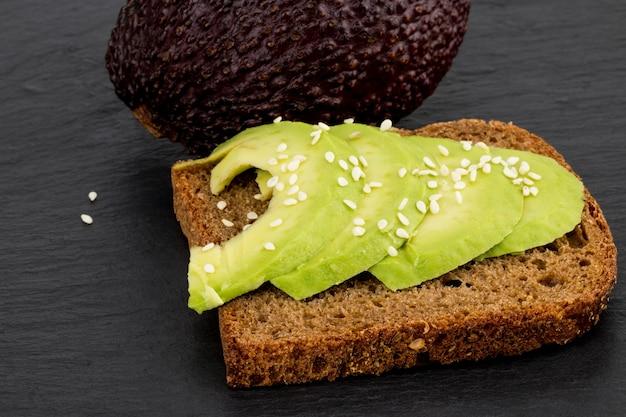 위에서 신선한 슬라이스 아보카도로 만든 어두운 호밀 빵에 아보카도 샌드위치.