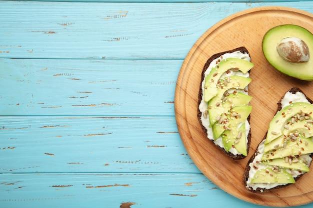 Сэндвич с авокадо на темном ржаном хлебе со свежими нарезанными авокадо на синем деревянном столе. вид сверху