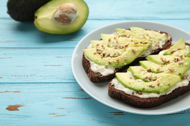 Сэндвич с авокадо на темном ржаном хлебе со свежими ломтиками авокадо. вид сверху