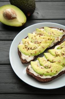 Сэндвич с авокадо на темном ржаном хлебе со свежими ломтиками авокадо