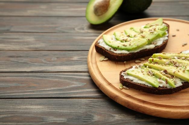 Сэндвич с авокадо на темном ржаном хлебе со свежими нарезанными авокадо