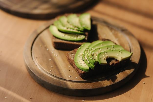 Сэндвич с авокадо на темном ржаном гренках, приготовленный со свежими нарезанными сверху авокадо. веганский