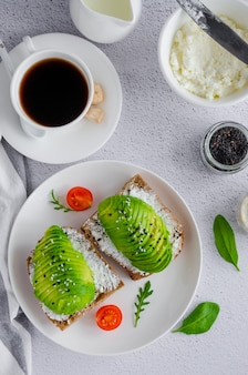 Avocado sandwich  with cream cheese and seeds on a white plate