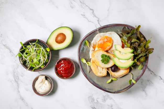 Avocado and sandwich with fried egg. tree sliced avocado and fried egg on toasted bread for breakfast.