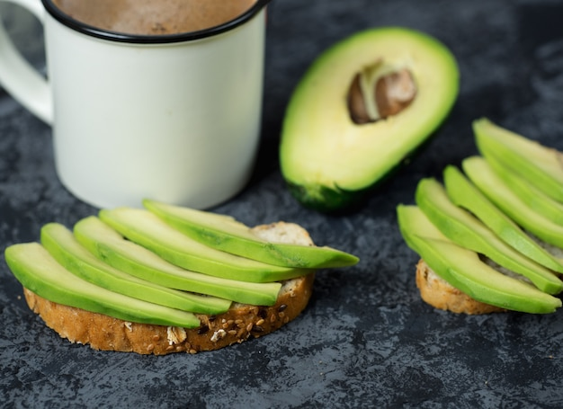 Avocado sandwiches breakfast and a cup of coffee