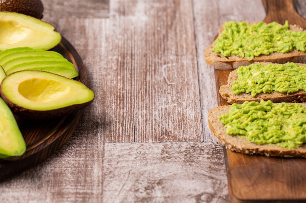 Бутерброды с авокадо рядом с нарезанными на деревянной доске.