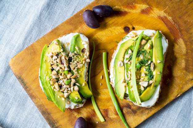 Avocado sandwiches with nuts and cream cheese on a cutting board