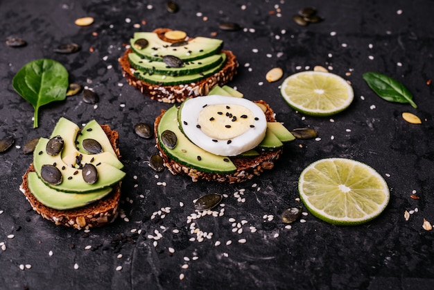 Avocado sandwiches with seeds, sesame and a lime.