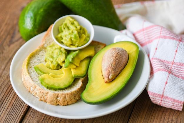 Avocado sliced half and avocado dip mashed on white plate