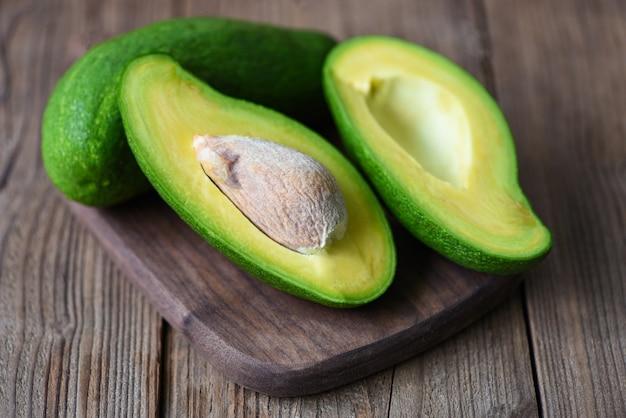 Avocado sliced half on wooden cutting board for avocado salad