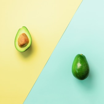 Avocado sliced with seed, whole fruit on blue and yellow background. minimal flat lay style.