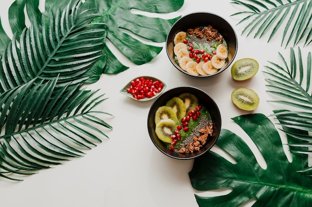 Avocado smoothie bowl topped with chia, granola, kiwi and  spinach.  overhead, top view, flat lay. healthy breakfast. tropical  leaves.
