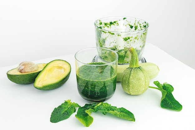 Avocado, spinach, zucchini and blender on white background