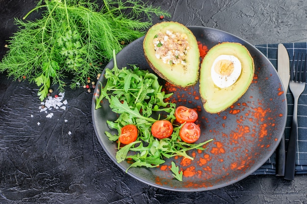 Avocado stuffed with eggs, tuna and sauce, arugula and dill on the black modern dish. black cutlery, napkin and background. keto diet healthy food.