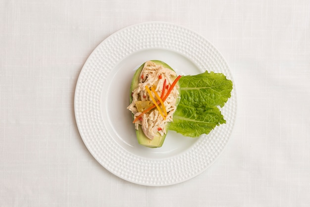 Avocado stuffed with lettuce and chicken. top view.