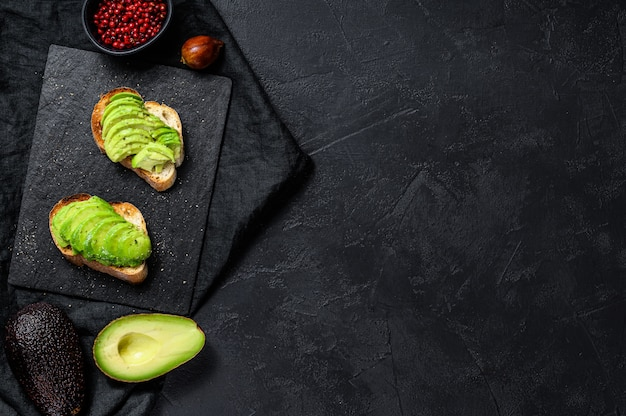 Avocado toast. black wall. top view. space for text