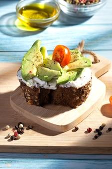 Тост с авокадо на синей деревянной основе с тенями, проникающими через кухонное окно. вертикальный формат.