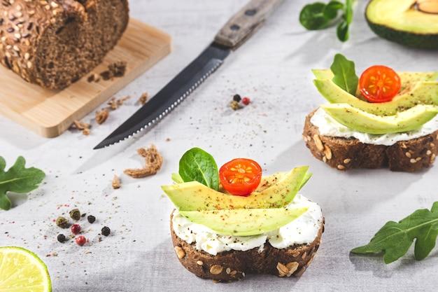 Гренки с авокадо на светлой основе. Premium Фотографии