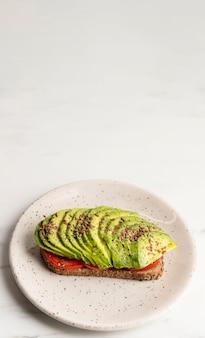 Pane tostato dell'avocado sulla zolla con lo spazio della copia