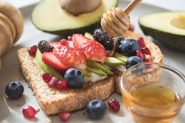 Avocado toast with berries topping on a plate on white wooden surface