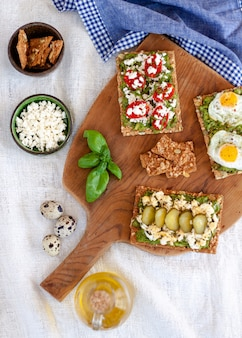 Avocado toast with cherry tomatoes, greek chees, eggs fried, cucumber and a basil twig