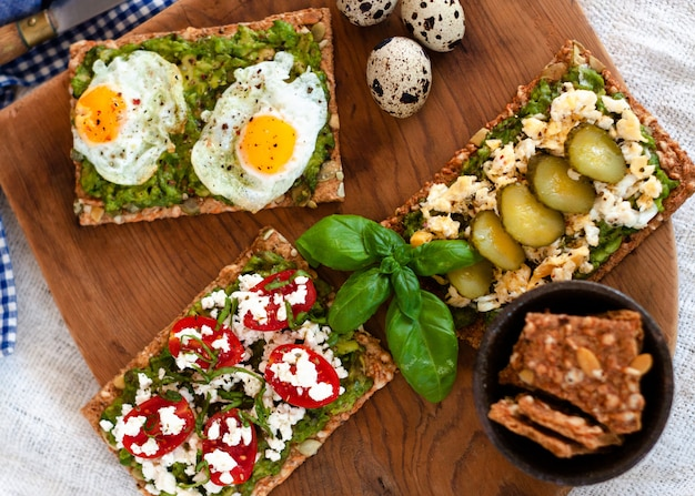 Avocado toast with cherry tomatoes, greek chees, eggs fried, cucumber and a basil twig.