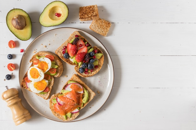 Avocado toast with different topping including salmon fish, eggs and berries