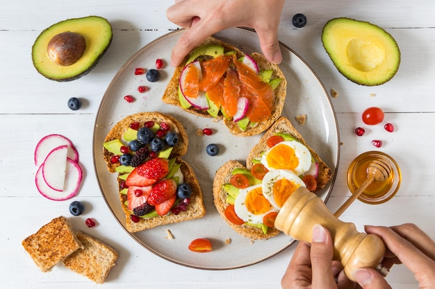 Avocado toast with different topping including salmon fish