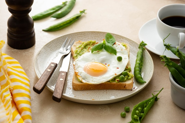 계란 후라이와 신선한 완두콩을 곁들인 아보카도 토스트, 커피 컵. 건강한 아침 식사, 케토 식품. 다이어트 개념입니다.