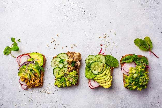 Avocado toasts with different toppings, top view, white background, copy space.