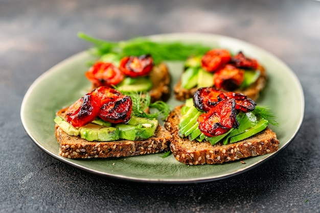 Avocado toasts with roasted tomatoes in a plate