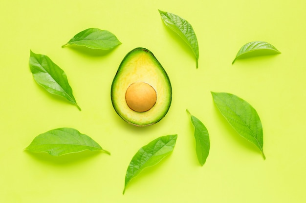 Avocado with leave on green background.