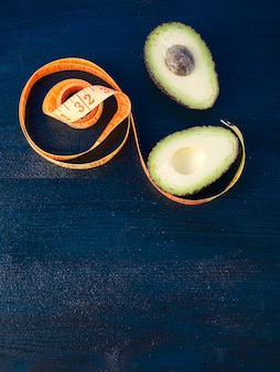 Avocado with measuring tape on table