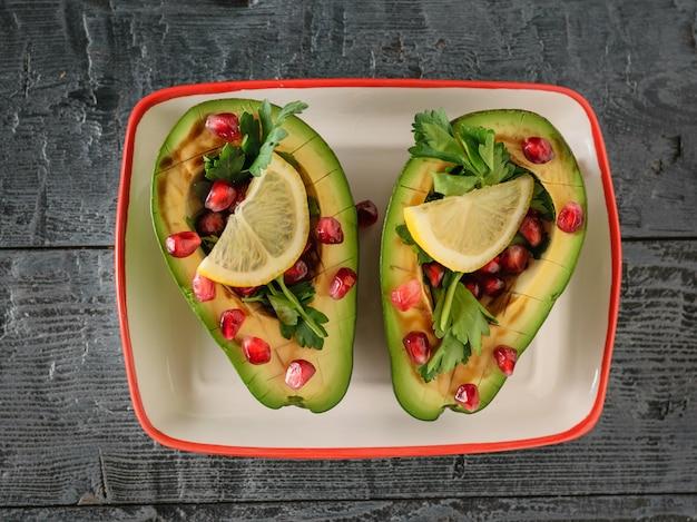 Авокадо с зернами граната, бальзамическим соусом и лимоном на темном черном столе. вегетарианская кухня для похудения. вид сверху.