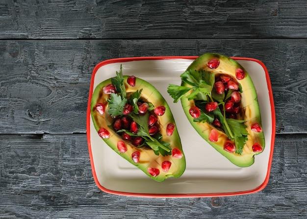 Авокадо с зернами граната, бальзамическим соусом и лимоном на столе