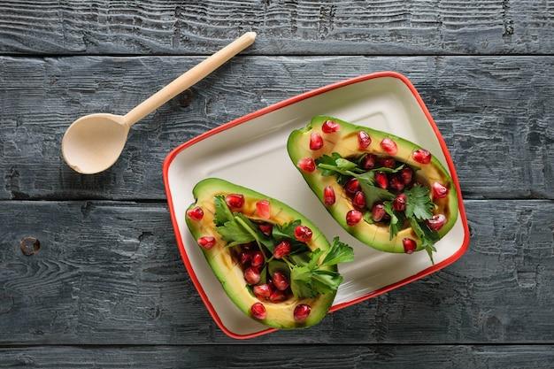 Авокадо с зернами граната, бальзамическим соусом, лимоном и зеленью и деревянной ложкой на черном столе