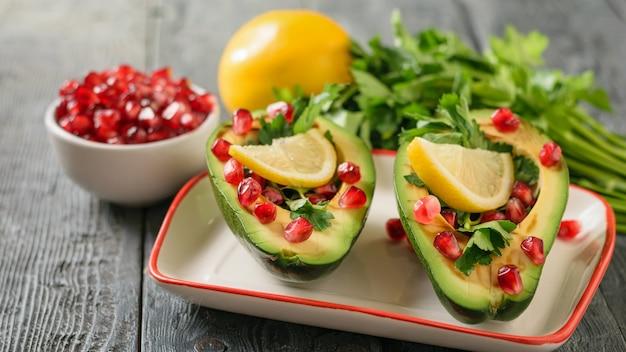 Авокадо с зернами граната, бальзамическим соусом, лимоном и зеленью на столе