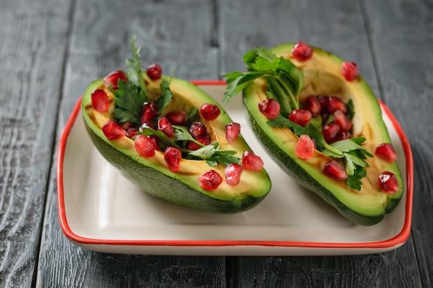 Авокадо с зернами граната, бальзамическим соусом, лимоном и зеленью в миске белого и красного света. вегетарианская кухня для похудения.