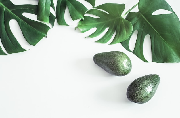 Avocado with tropical leaves on white background