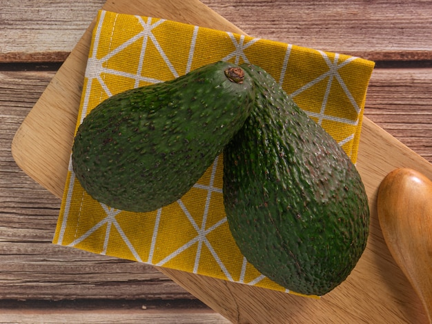 The  avocado on wood table top view image for food concept.